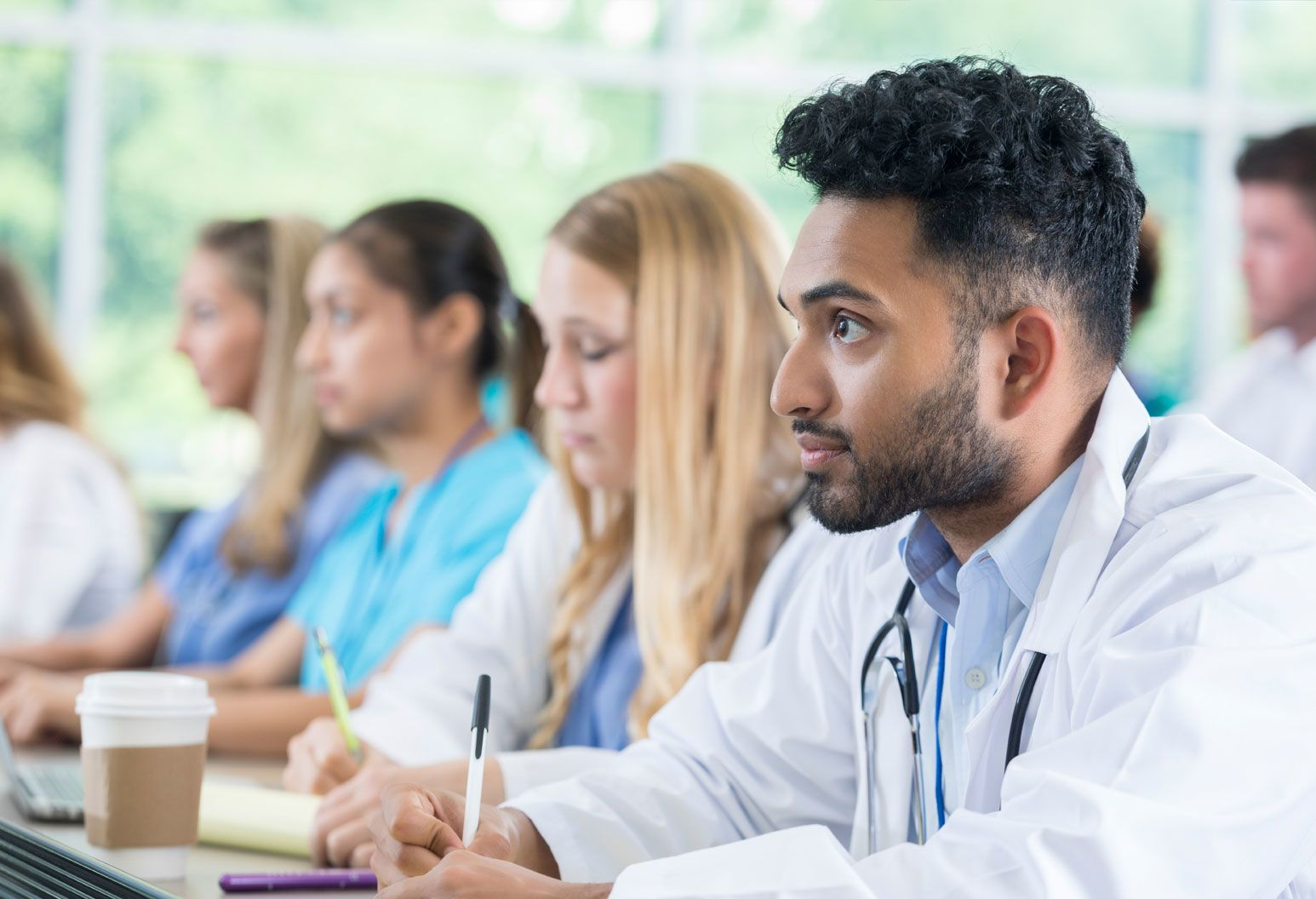 Medical professionals in a classroom setting. Male wearing stethoscope in the foreground looking engaged.