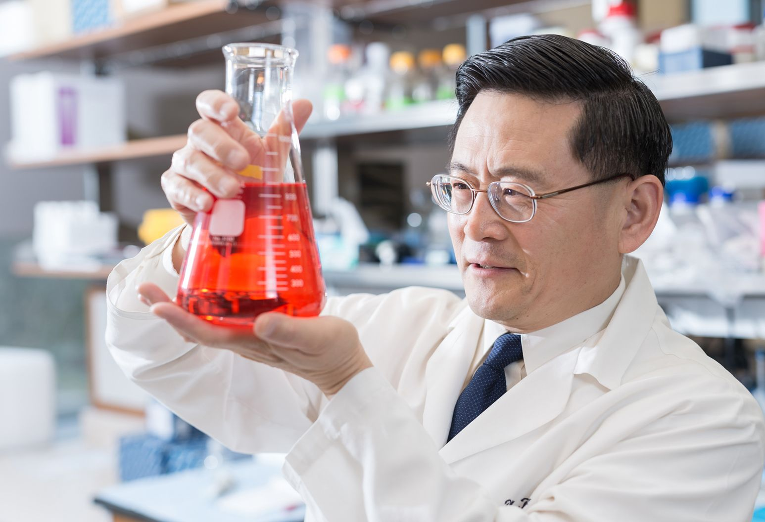Researcher Ping Wang is examining a beaker with red liquid in it.