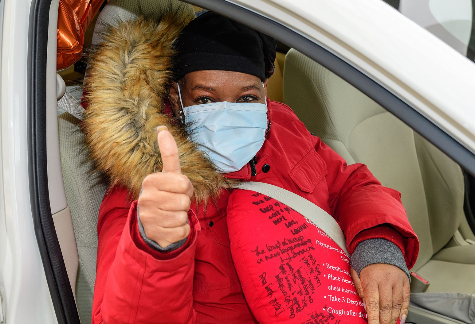 A woman in a black cap and red winter coat with a fur lined hood sits in a car. She has a red pillow against her chest and she gives the camera a thumbs up.