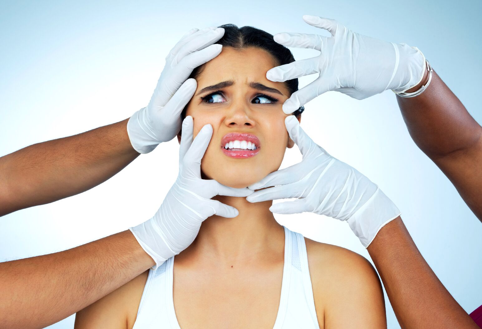 woman's face being touched by multiple hands with surgical gloves on.