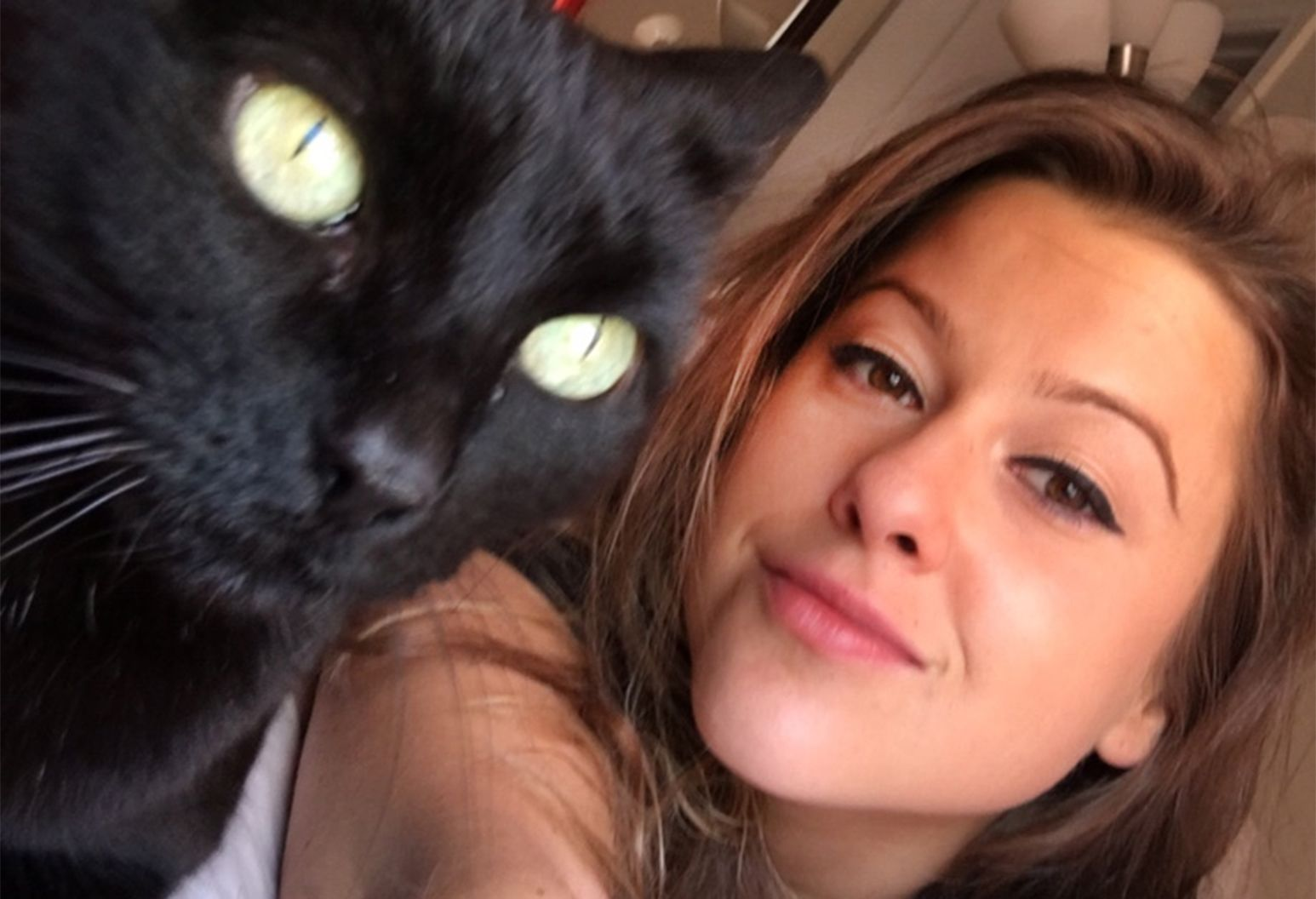 A smiling woman takes a picture with her black cat.