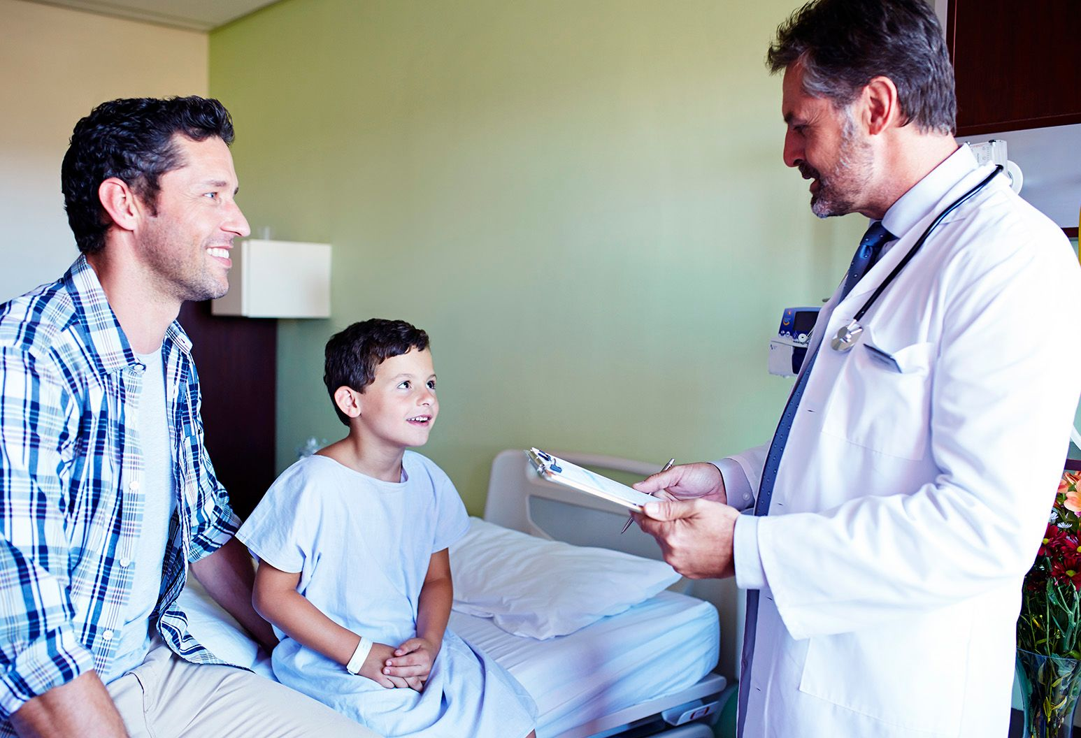 A little boy wearing a hospital gown sits on a bed in a patient room next to his father. They are talking to a male doctor, who is standing beside the bed and holding a clipboard.