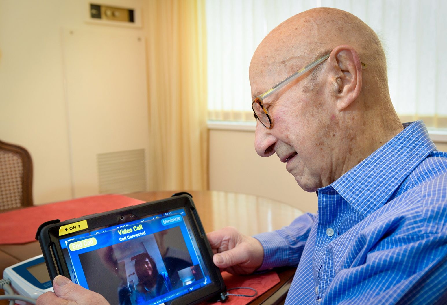 An elderly man views a clinician using a telehealth device