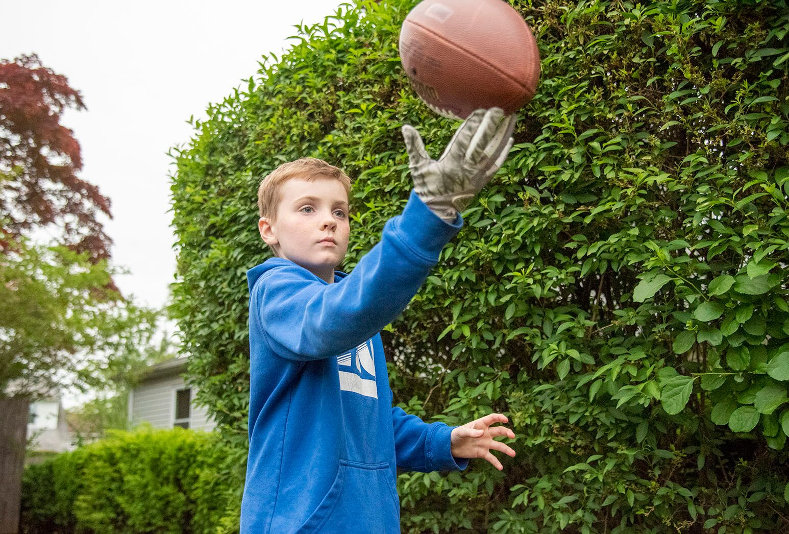 Young boy with dark hair in a blue sweatshirt playing outside with a football.