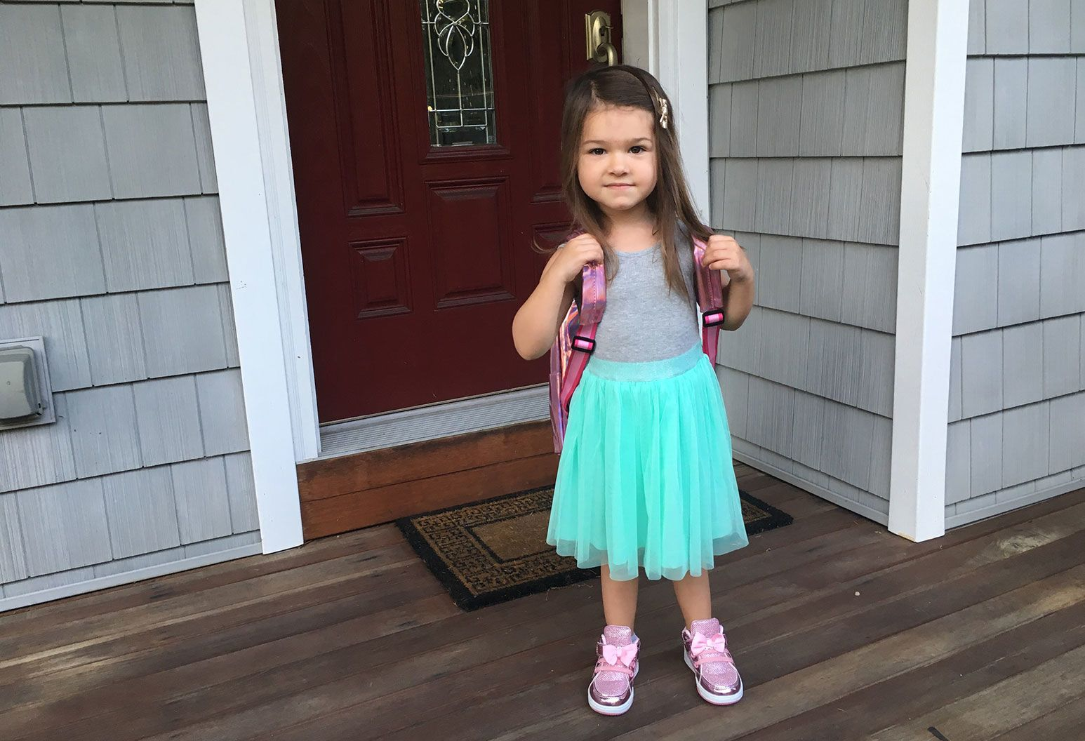 A toddler with long hair, a purple book bag, grey top and teal lace skirt stands in front of a doorway posing for a photo. She has a determined look on her face.