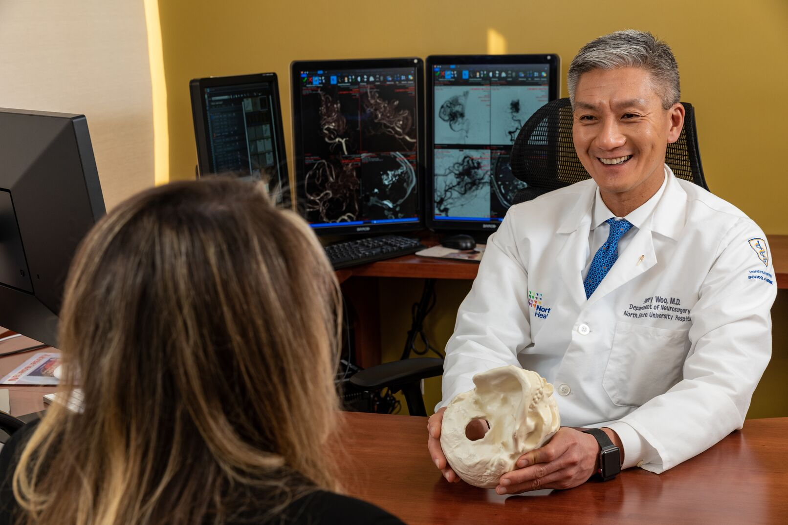 Henry Woo, MD, discusses treatments with a patient. He says two to four percent of people in the US will suffer from a brain aneurysm, 20-percent of which will have multiple aneurysms