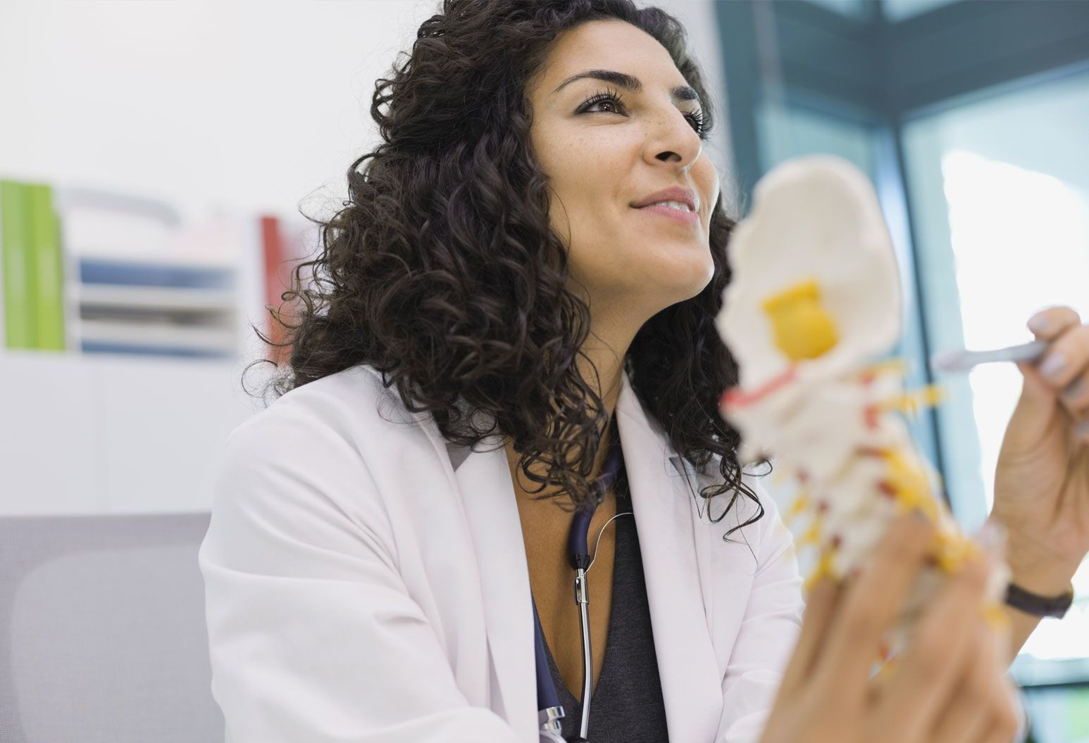 A female doctor holds a model of a spine and looks out of camera. She has dark, curly hair and wears a stethoscope around her neck.