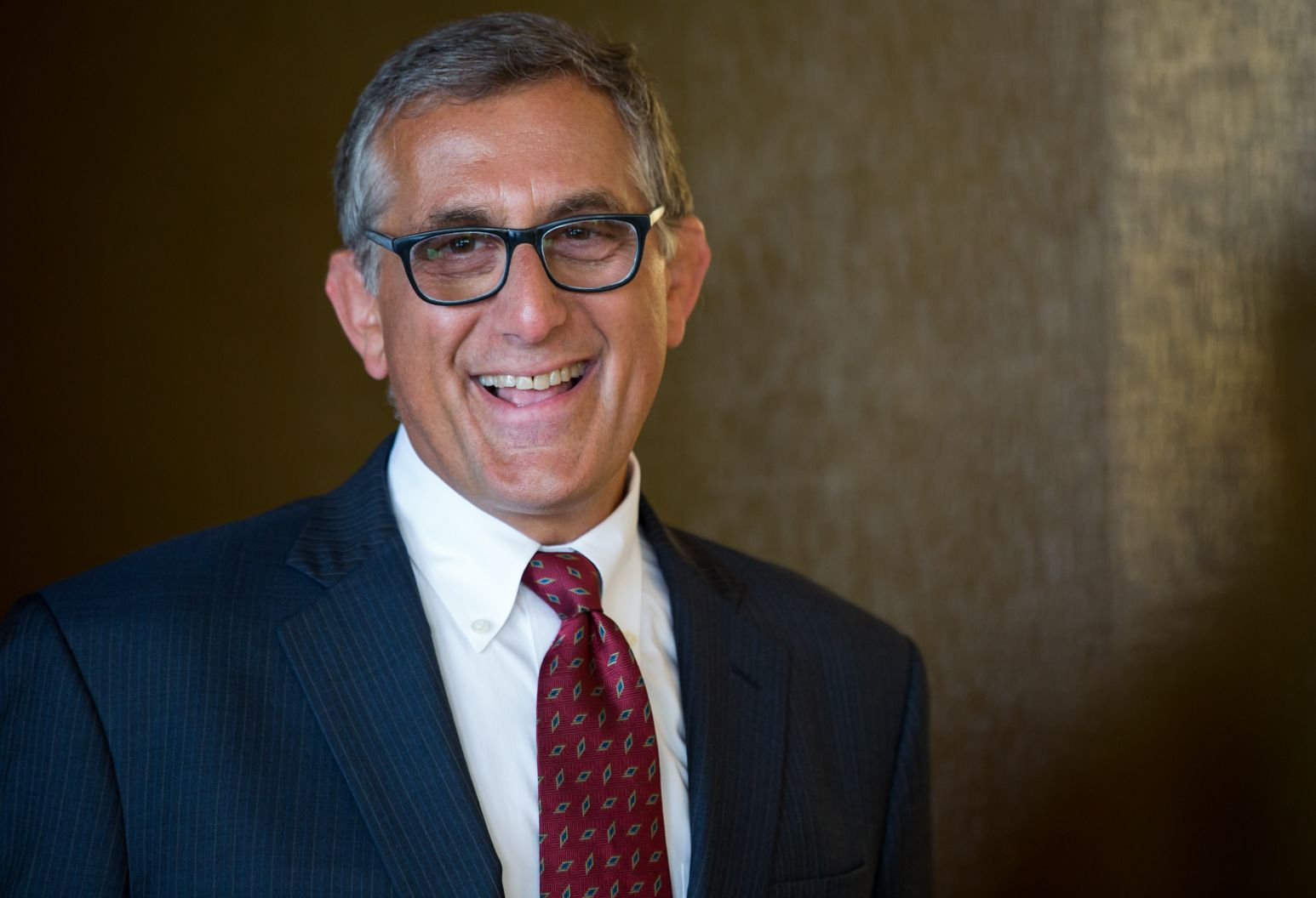 A man in a blue pin stripe suit, white collar button down shirt, and a red tie smiles at the camera. He has grey salt and pepper hair and wears black rimmed glasses.