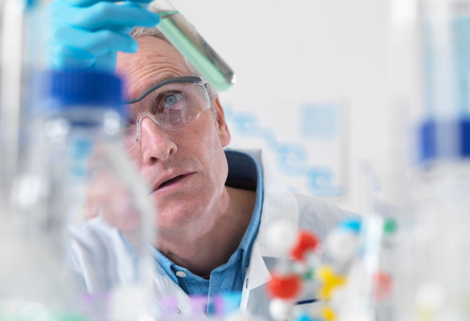 Man in a lab coat and safety goggles looking at a test tube speciment
