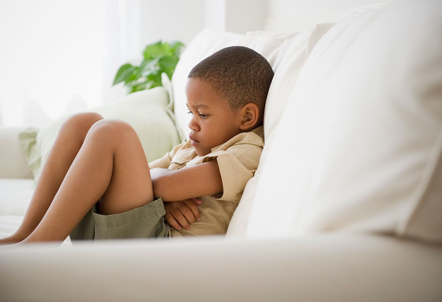 Sad child sits with his arms folded on a white couch.