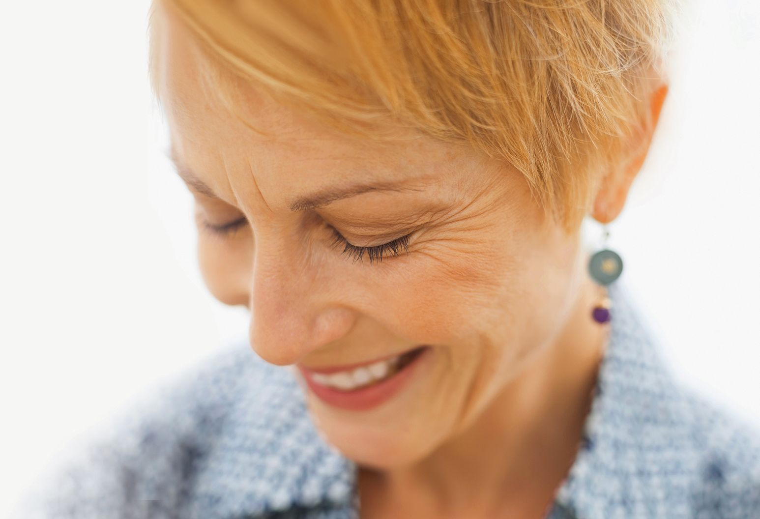 Mature woman smiling with head bent and eyes closed