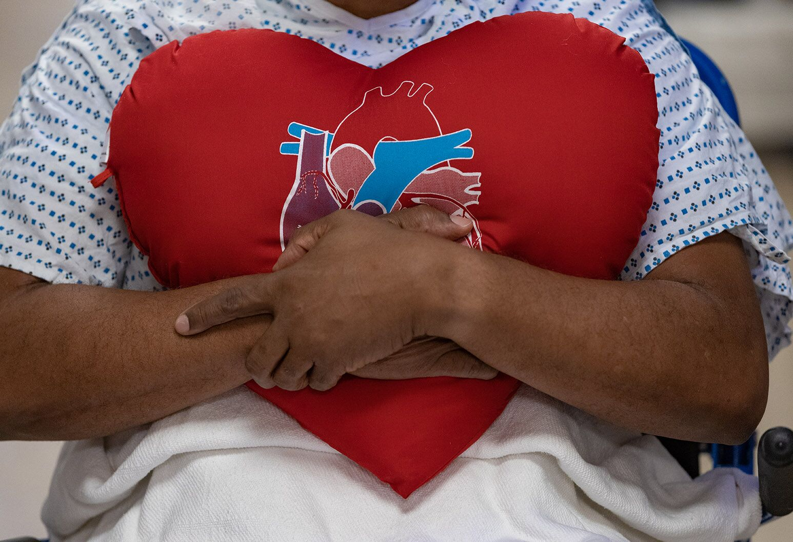 Close up of a patient's chest. They have their arms crossed around a heart shaped pillow.