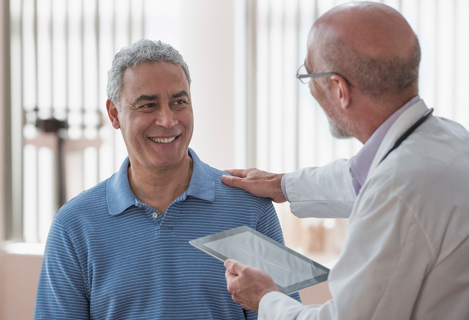 Doctor placing his hand on patient reassuringly as patient smiles at him