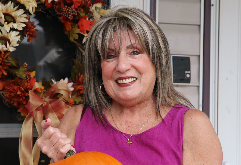 Josephine Serino smiles and holds a pumpkin as she poses in front of her home. A fall wreath hangs from a door behind her.