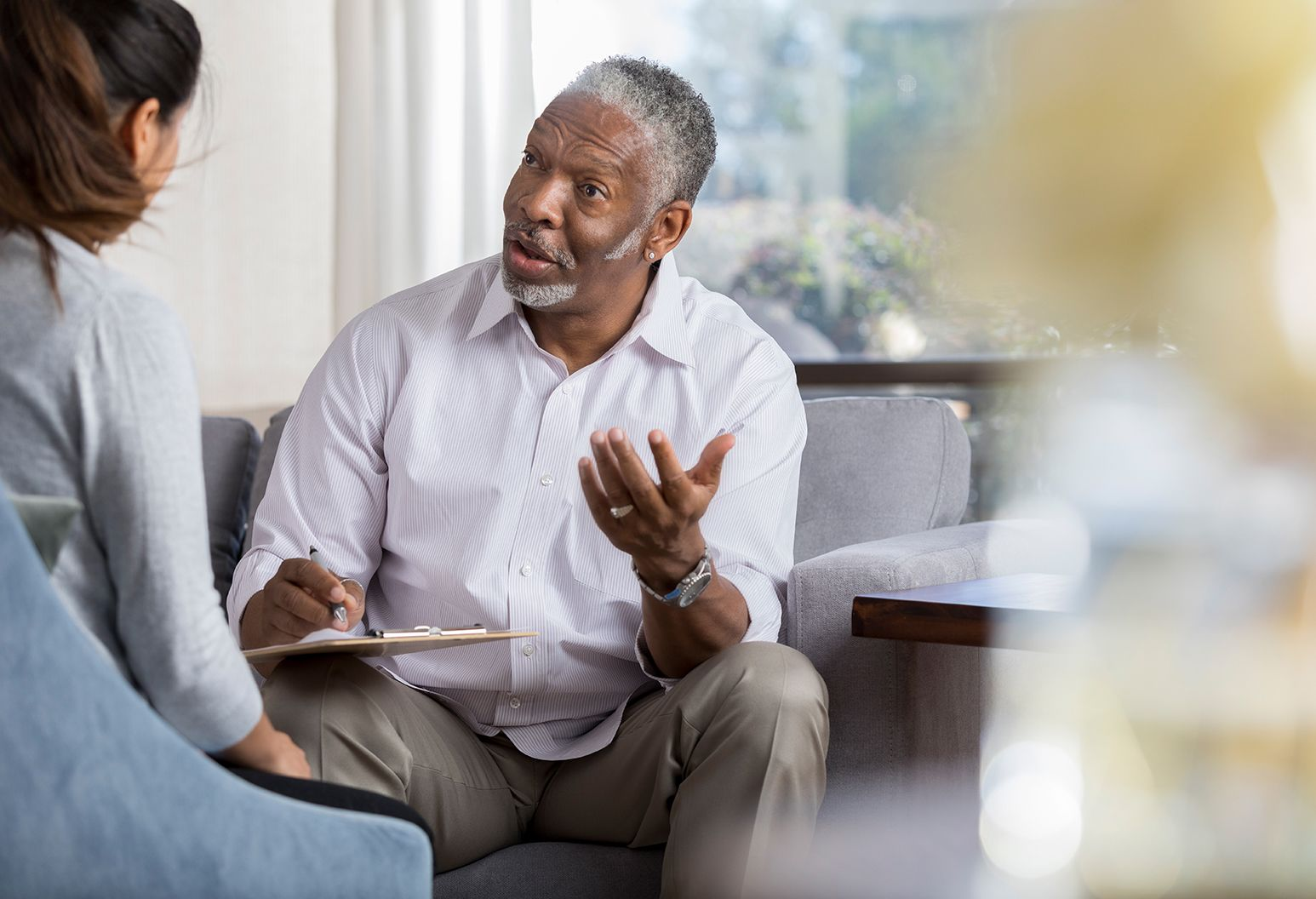 Confident senior African American male counselor gestures as he gives advice to a female patient. The counselor is holding a clipboard.
