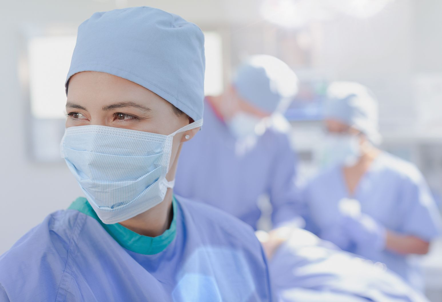Smiling female surgeon wearing surgical mask in operating room