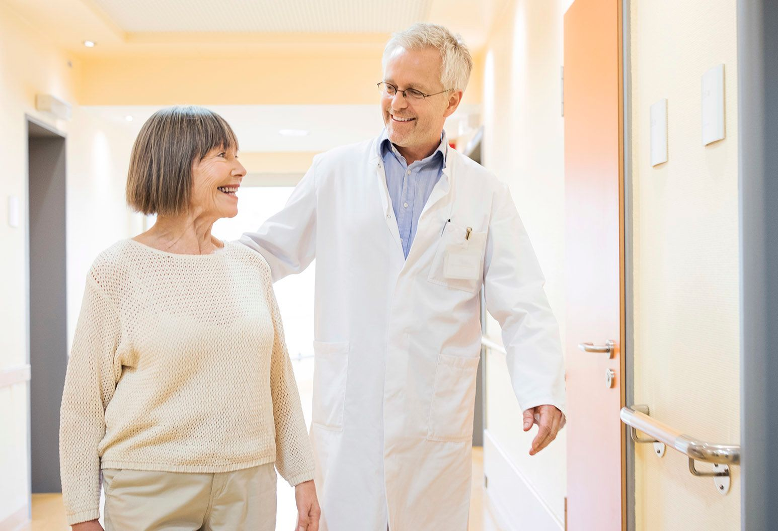 Mature male doctor in white lab coat is walking with senior woman in corridor of hospital