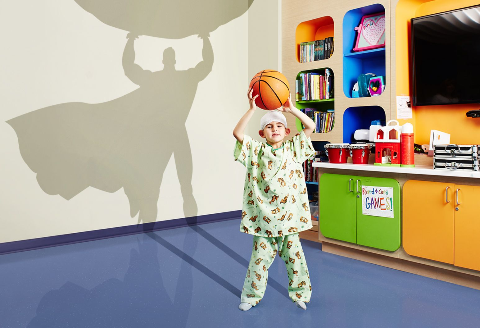 A young male patient wearing green animal printed hospital clothes stands in a colorful room proudly holding a basketball over his head. There's a shadow of a superhero on the wall behind him.