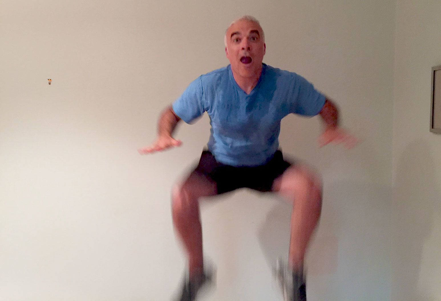 A man with short white hair in a sweaty blue shirt and black shorts is jumping so his hands can touch his knees.