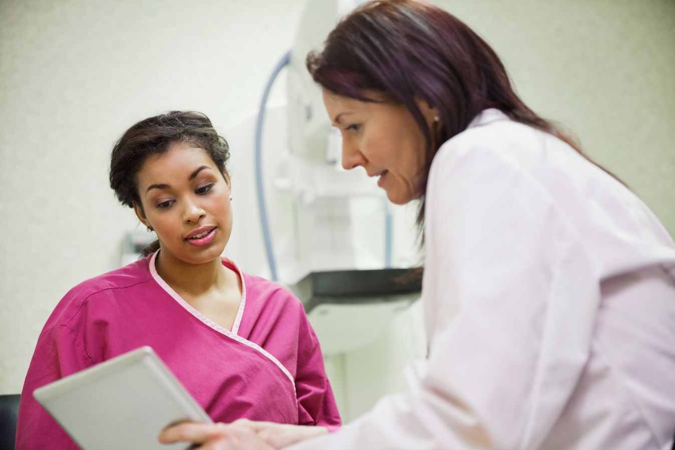 Patient in pink hospital gown talking to a doctor about her results
