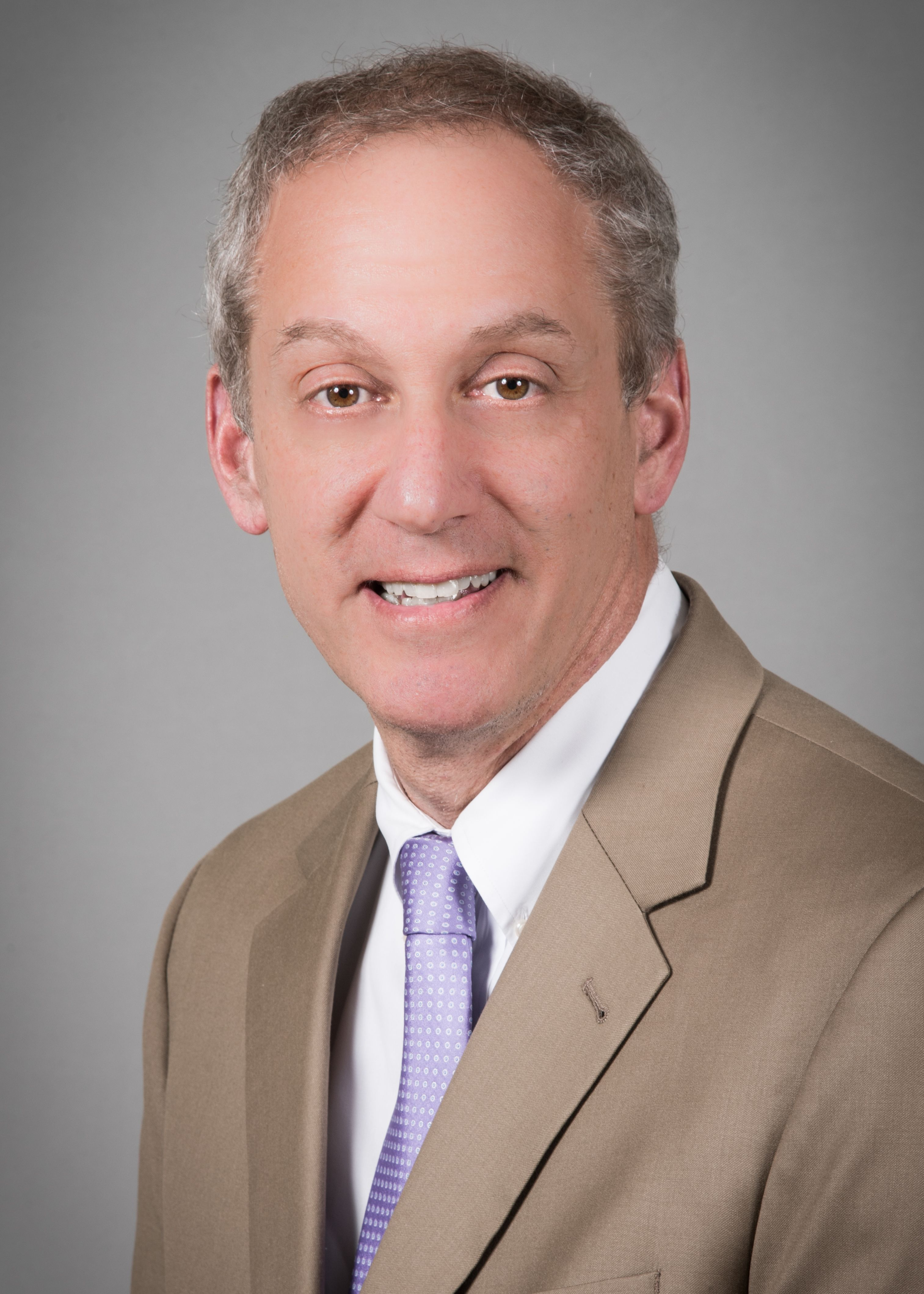 Peter Silver, MD, wearing a beige suit and purple tie