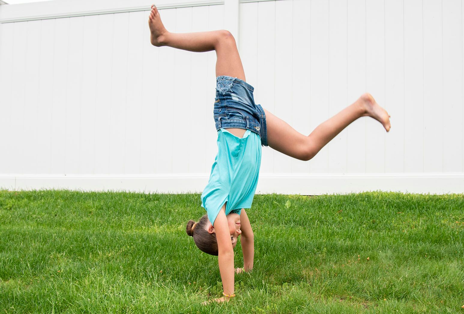 Young girl on the grass mid-cartwheel in a blue top and blue jean shorts in front of a white fence.