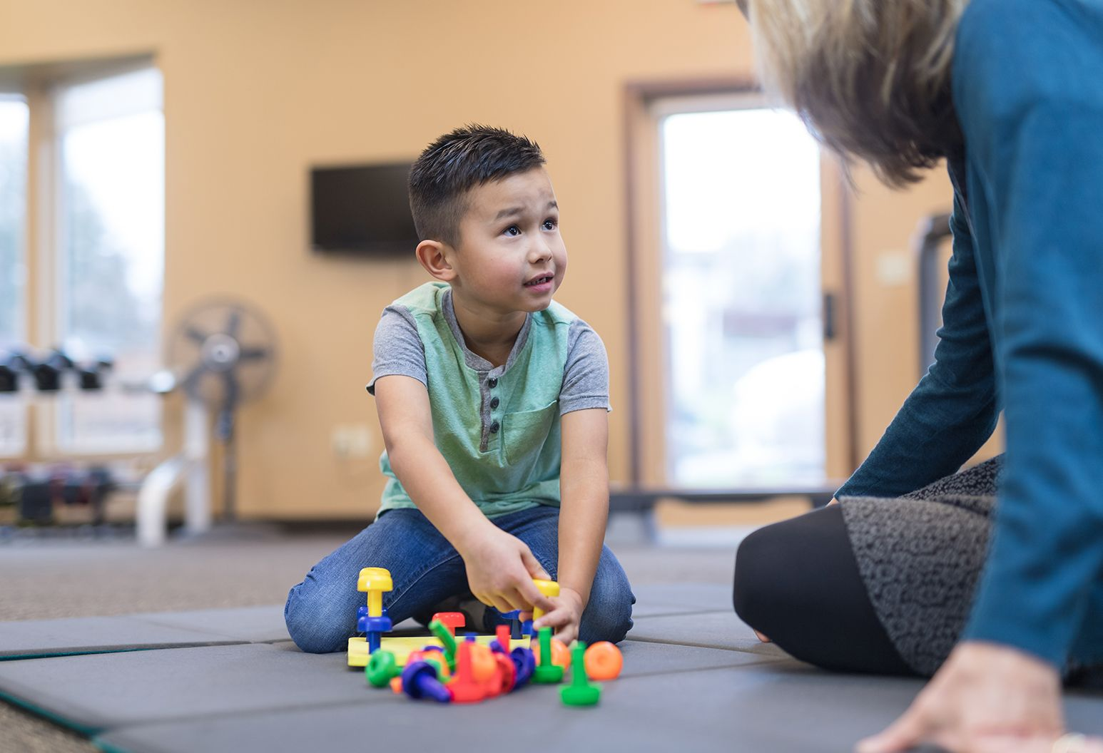 An occupational therapist sits on the floor with an elementary-age  boy, working on his fine motor and coordination skills.
