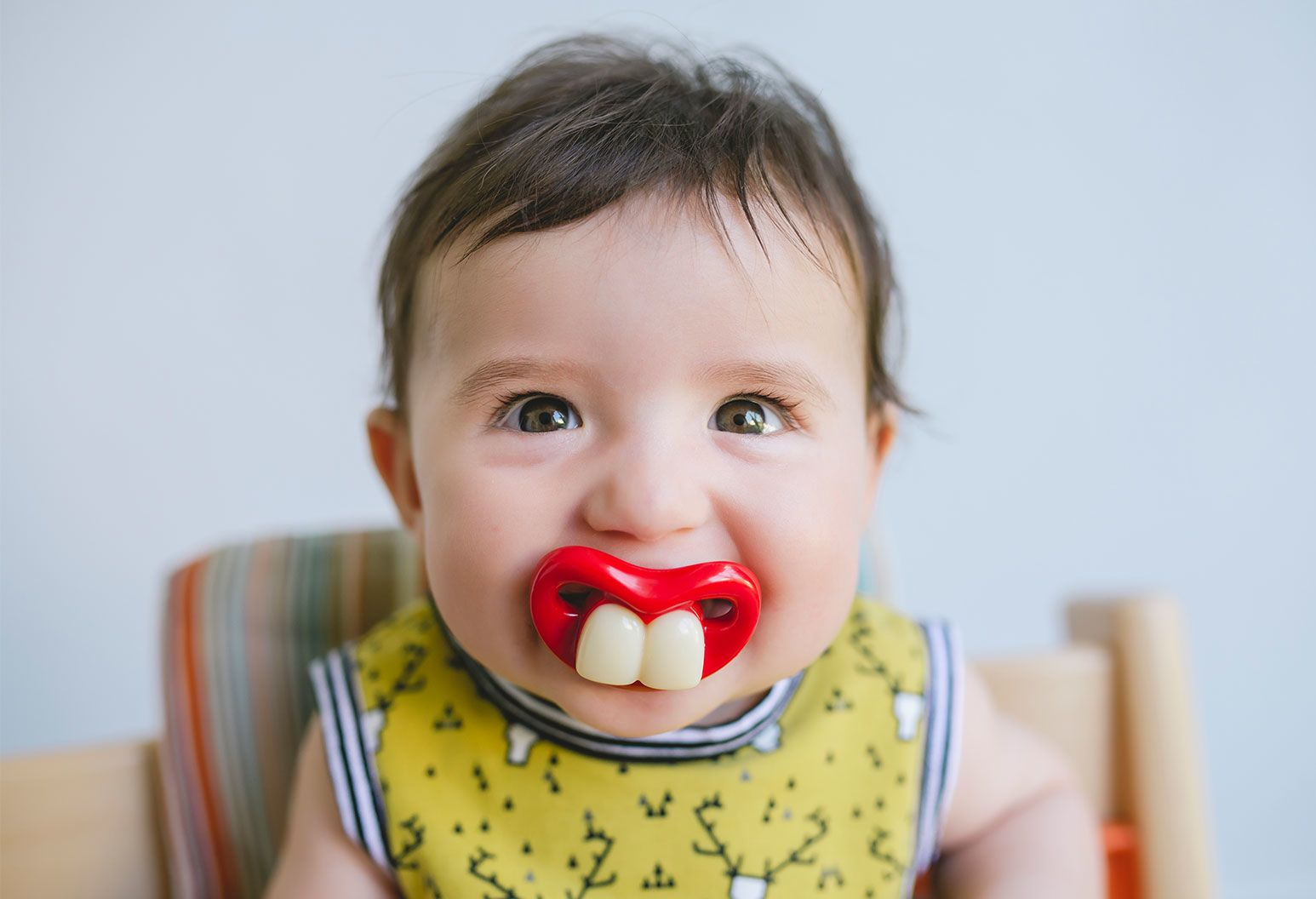 Baby sits in a highchair with a yellow sleeveless shirt on with a pacifier in their mouth. The pacifier is read and has two front teeth molded on to make it look like the baby is smiling to show their teeth.