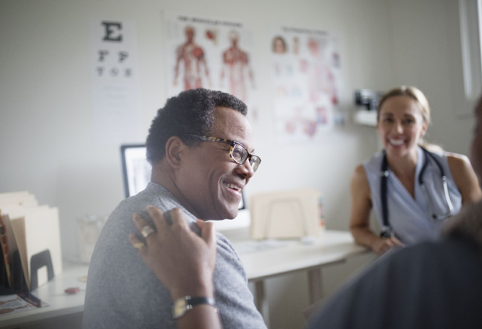 A man wearing glasses smiling talking to a doctor.