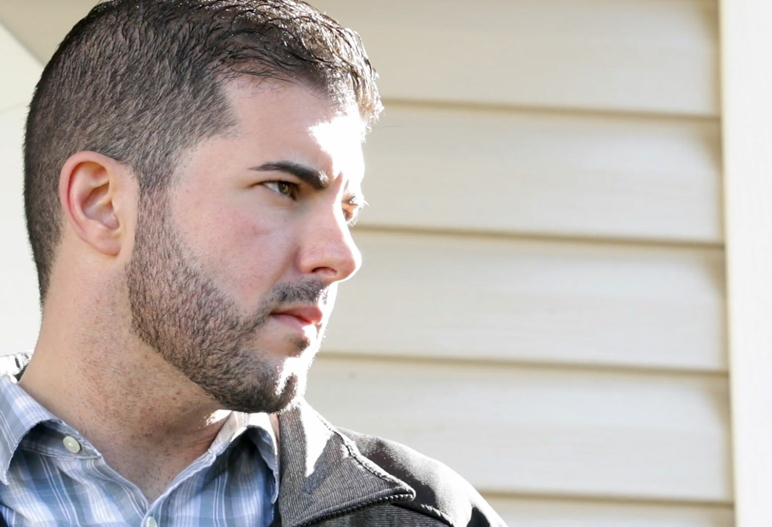 A man with short black hair and nicely trimmed beard looks off camera as the sun shines on his face.
