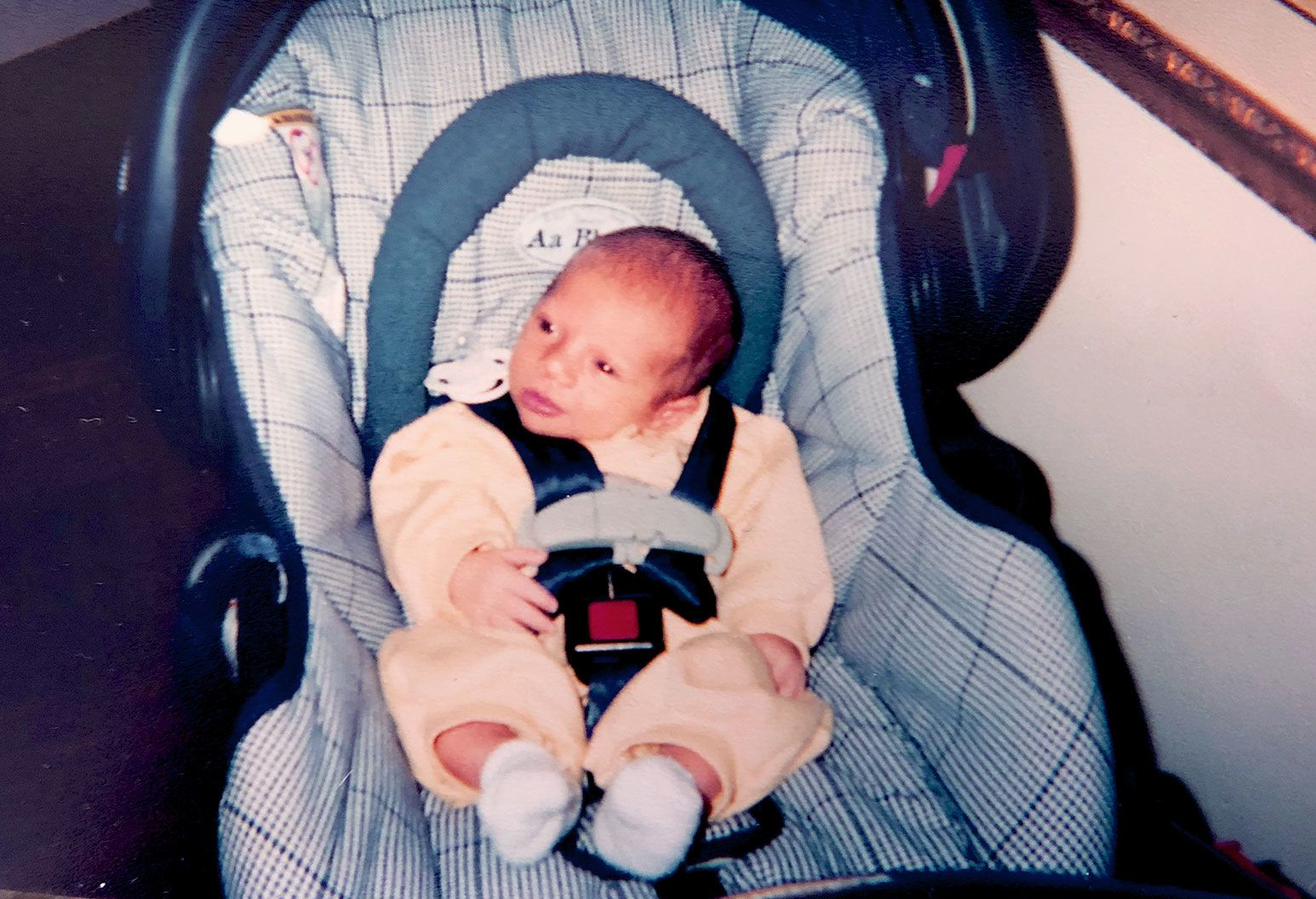 A newborn baby in a yellow onesie sits in a blue cushioned car seat.