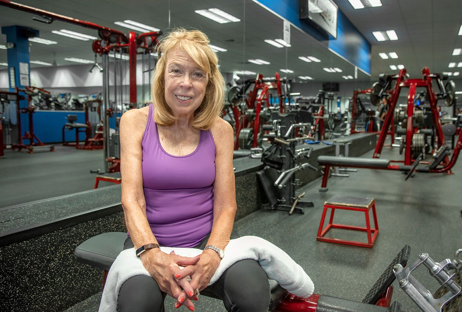 Blonde haired woman in purple tank top sits on gym equipment.