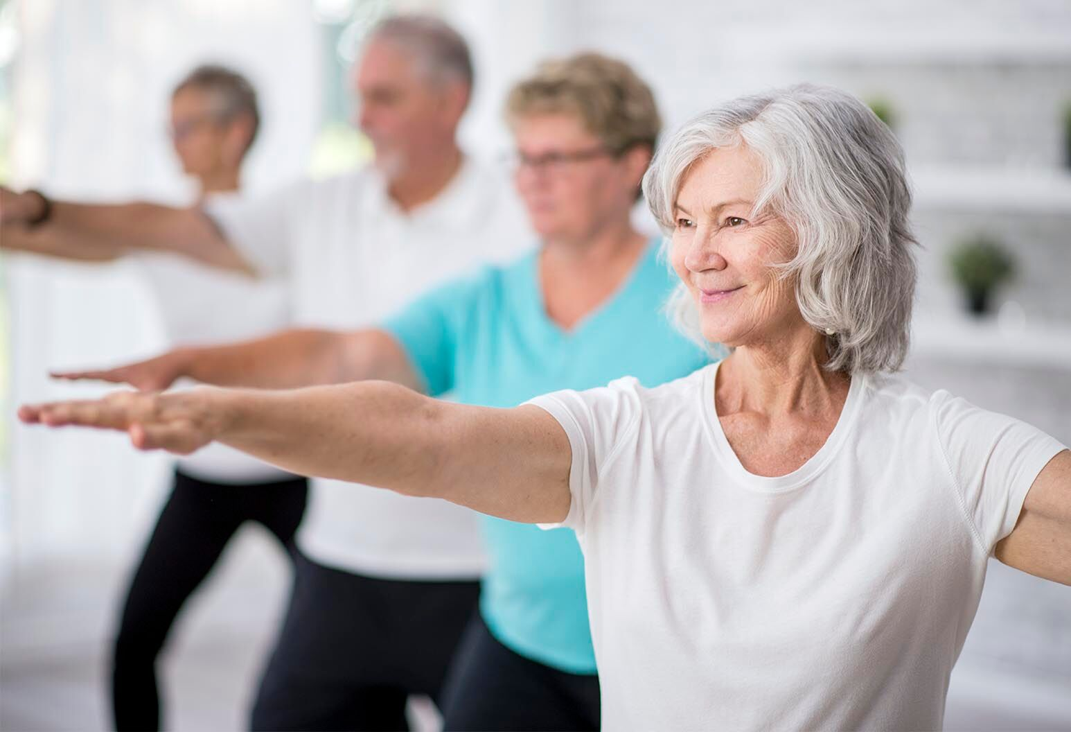 A multi-ethnic group of adult men and women are indoors in a fitness studio. They are wearing casual clothing while at a Tai Chi class. A senior Caucasian woman is smiling while stretching out her arms.