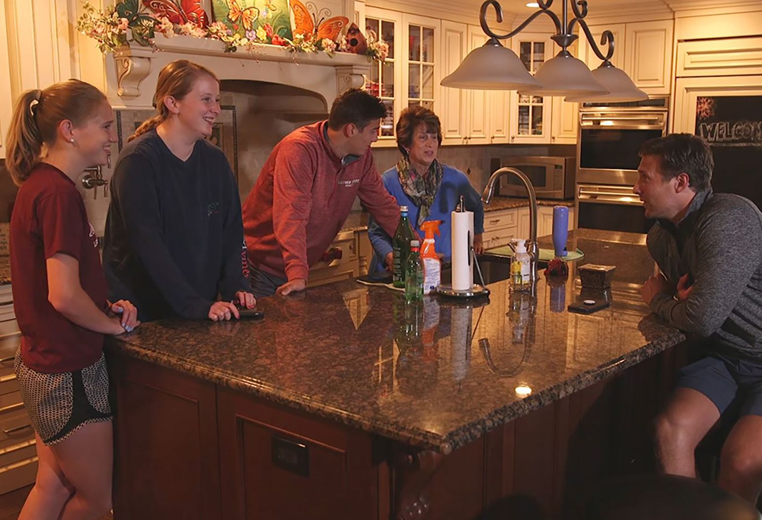 A family of five stands around a kitchen counter laughing and chatting.