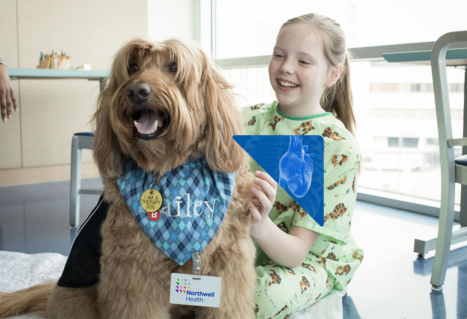 Young girl in hospital with pet therapy dog.