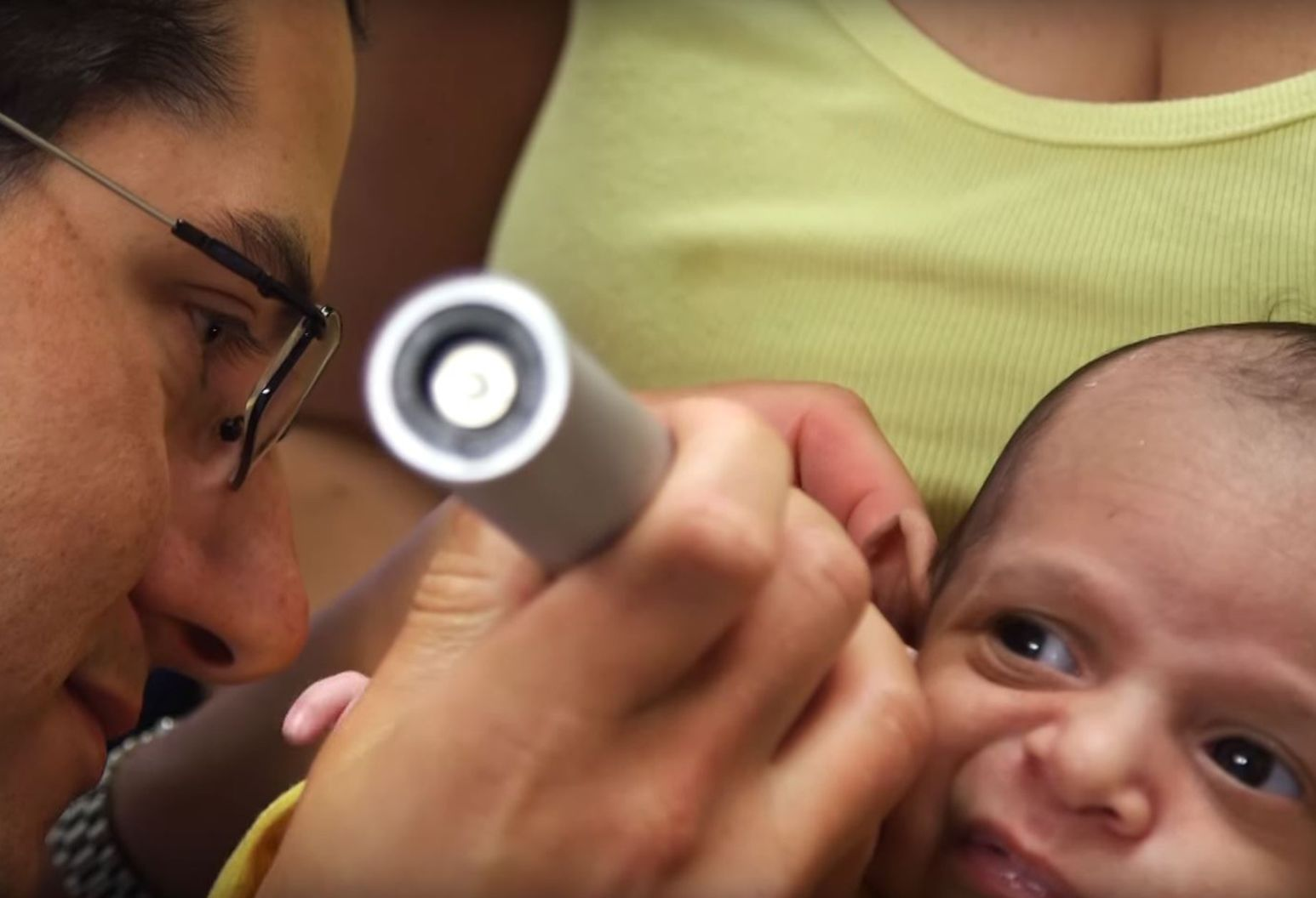 Dr. Lee Smith, a pediatric otolaryngologist, examines a baby's ear.