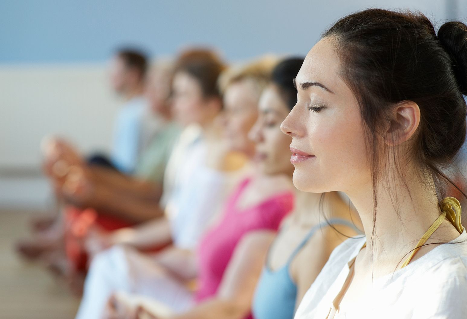 Row of woman with their eyes closed, doing yoga
