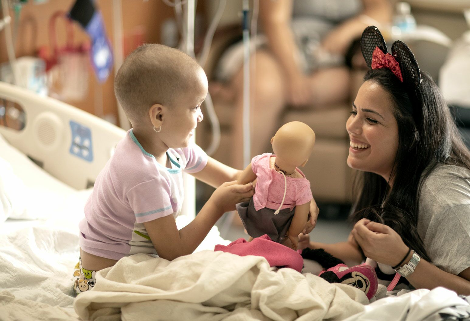A young girl sitting up in a hospital bed holding a baby doll. A young woman kneeling at the edge of the bed is smiling.