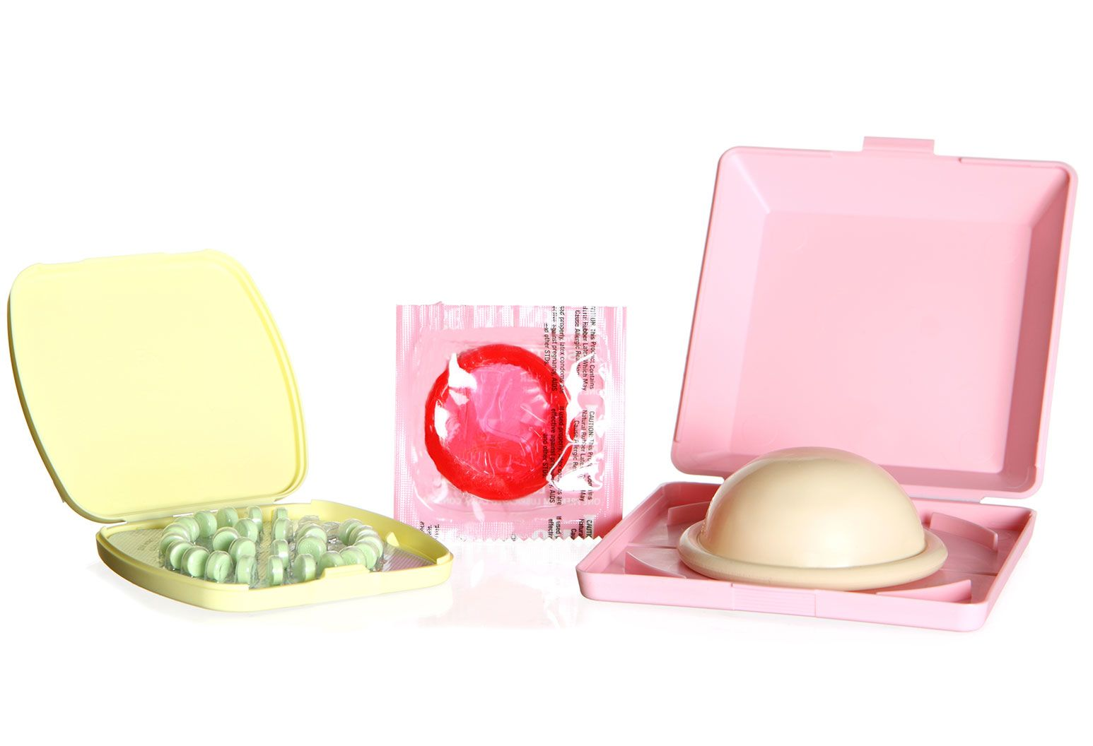 A yellow pill box containing green pills, an upright red latex condom in packaging, and a pink box holding a diaphragm are positioned next to each other.