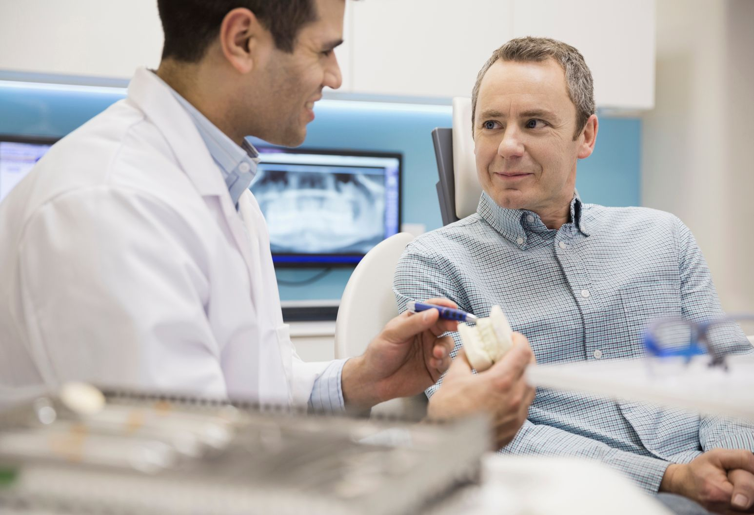 Dentist and male patient discussing teeth