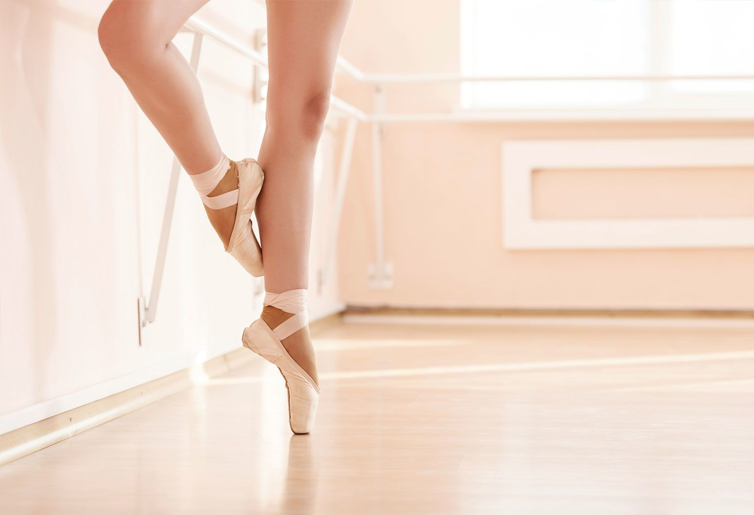 A ballerina with bare legs is wearing pink satin pointe shoes and standing on one leg, on her toes. The other leg is pointed on her calf. She's in an empty dance studio with wood floors and a white barre.