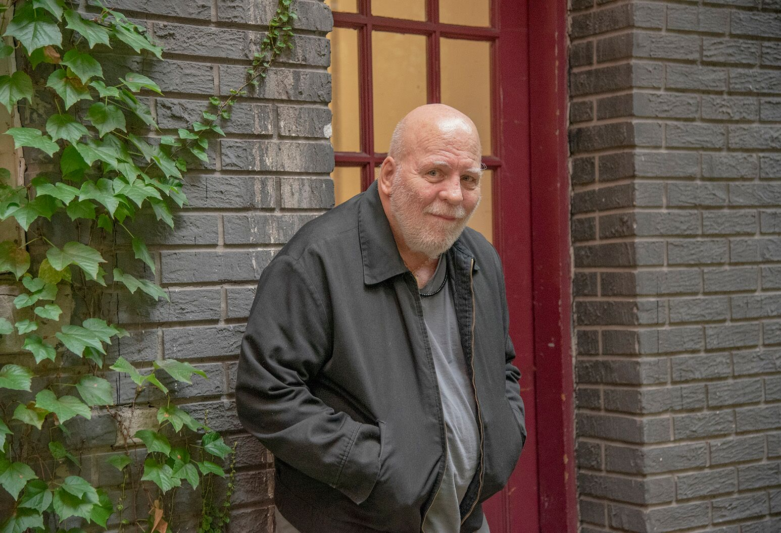 Older man in a dark gray coat, leaning against a brick wall and red door with his hands in pockets.