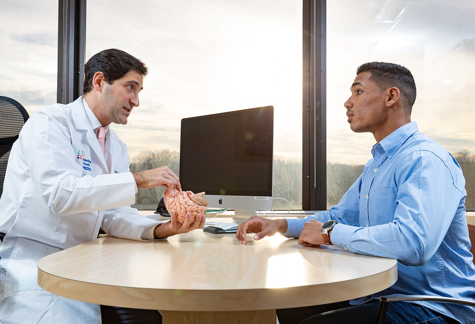 A doctor in a white lab coat holding a model brain, talking to a man in a blue shirt sitting across the desk.