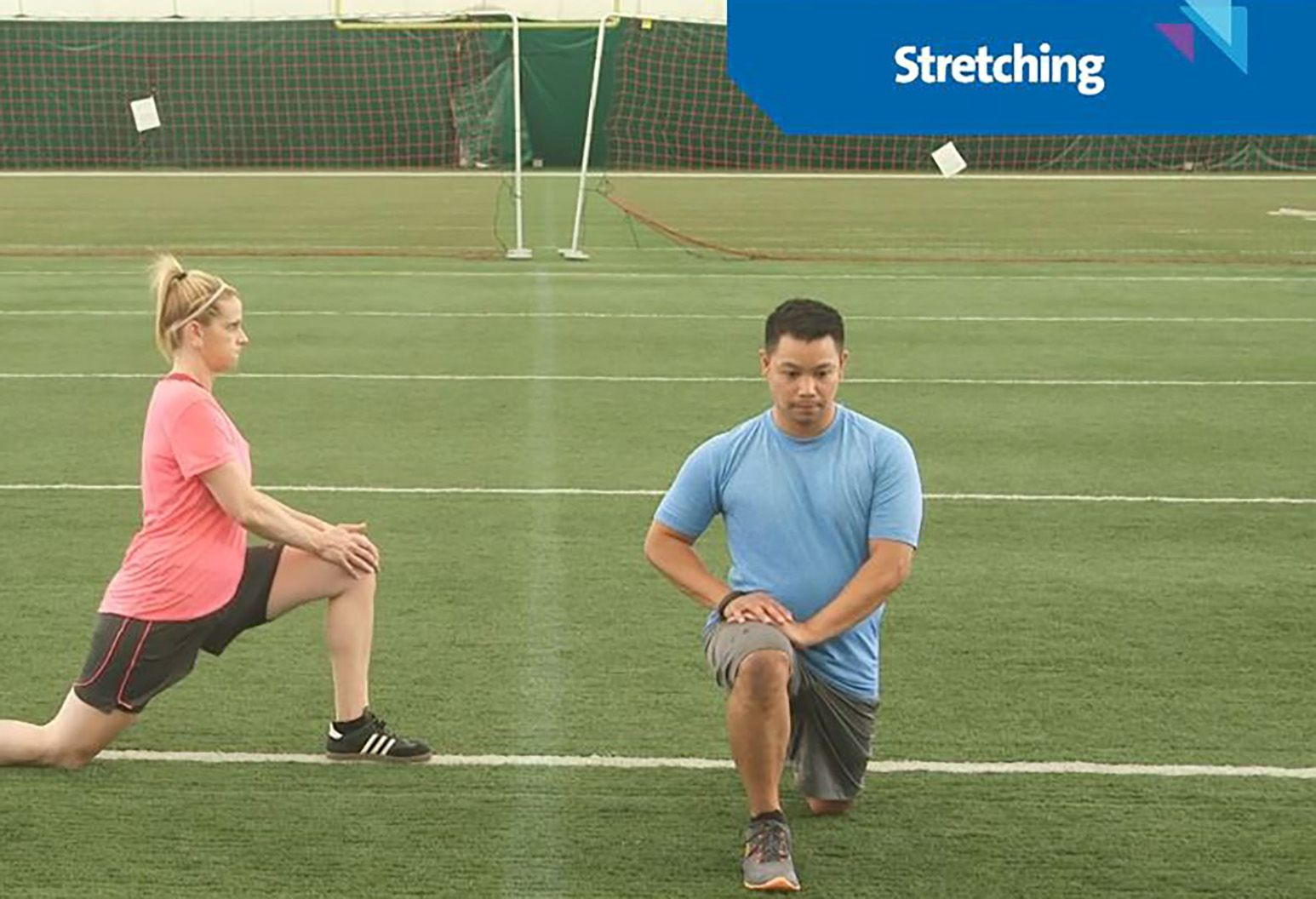 A man and woman stretching out their quad muscles, using each other for support