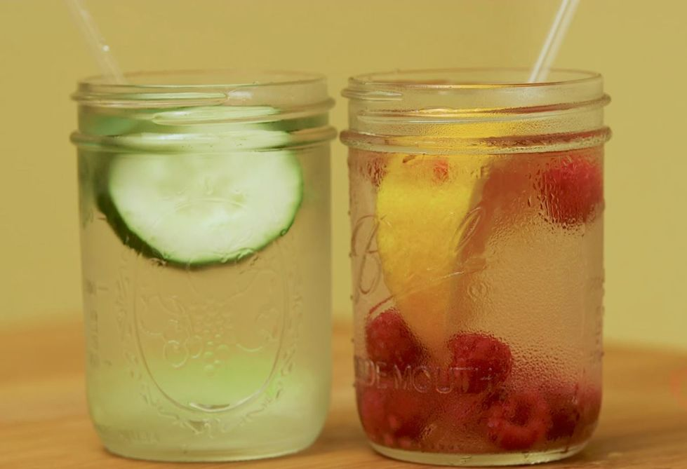 Two jars of water with cucumber, lemon and raspberries inside