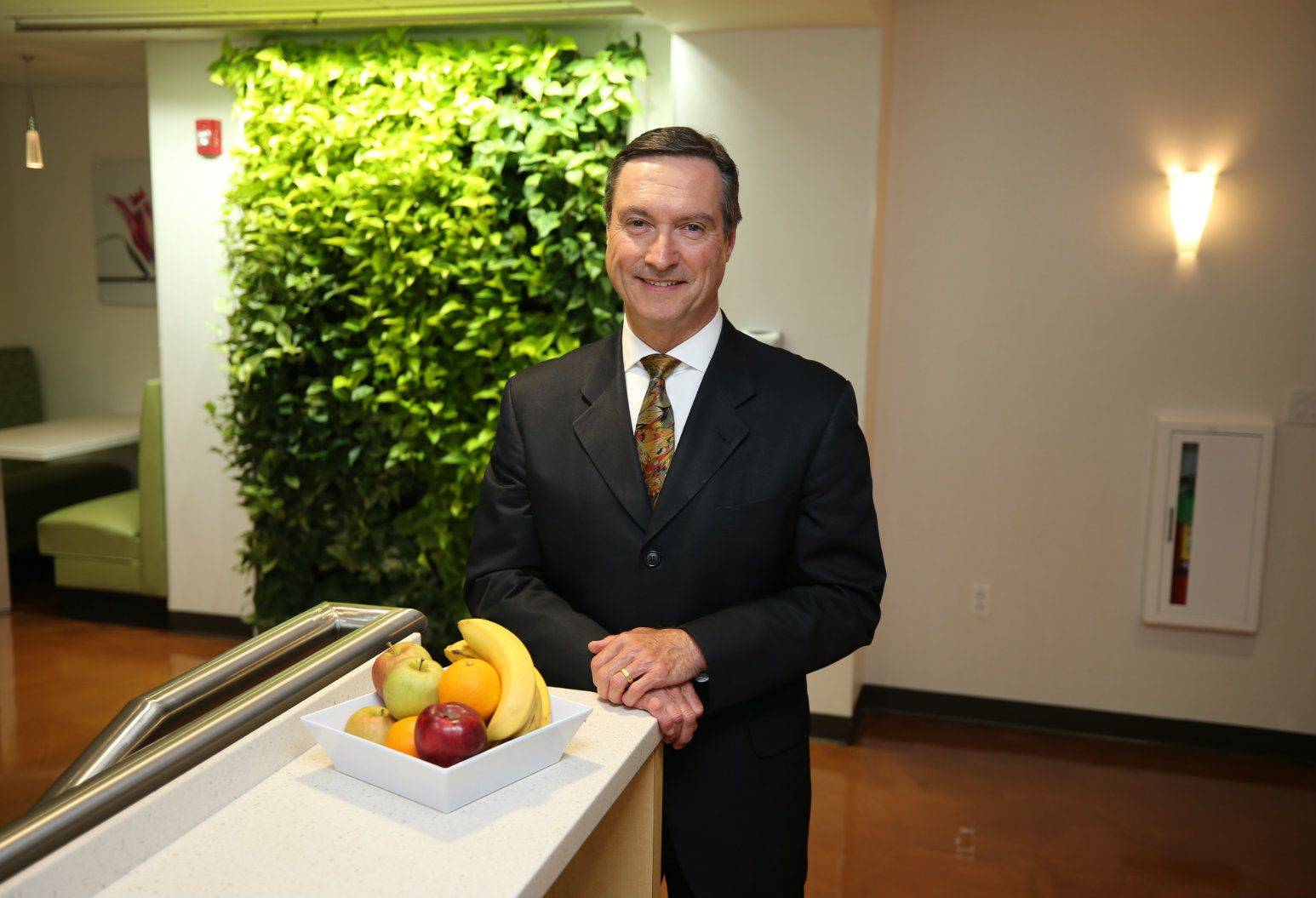 Bruno Tison, smiling and wearing a black suit with a colorful tie, leans against a counter in a hospital cafeteria. On the counter sits a square bowl of fruit containing bananas, apples, and oranges. Behind him, there is a seating booth and a decorative wall of vegetation against a plain white wall. As the first Michelin Star chef hired by a U.S. healthcare organization, Bruno Tison is shaking up hospital food for Northwell Health.