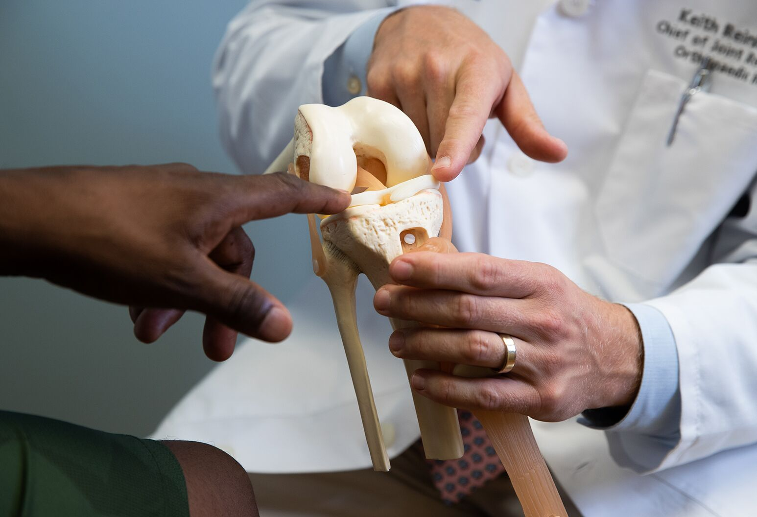 A doctor pointing at a model of a bone
