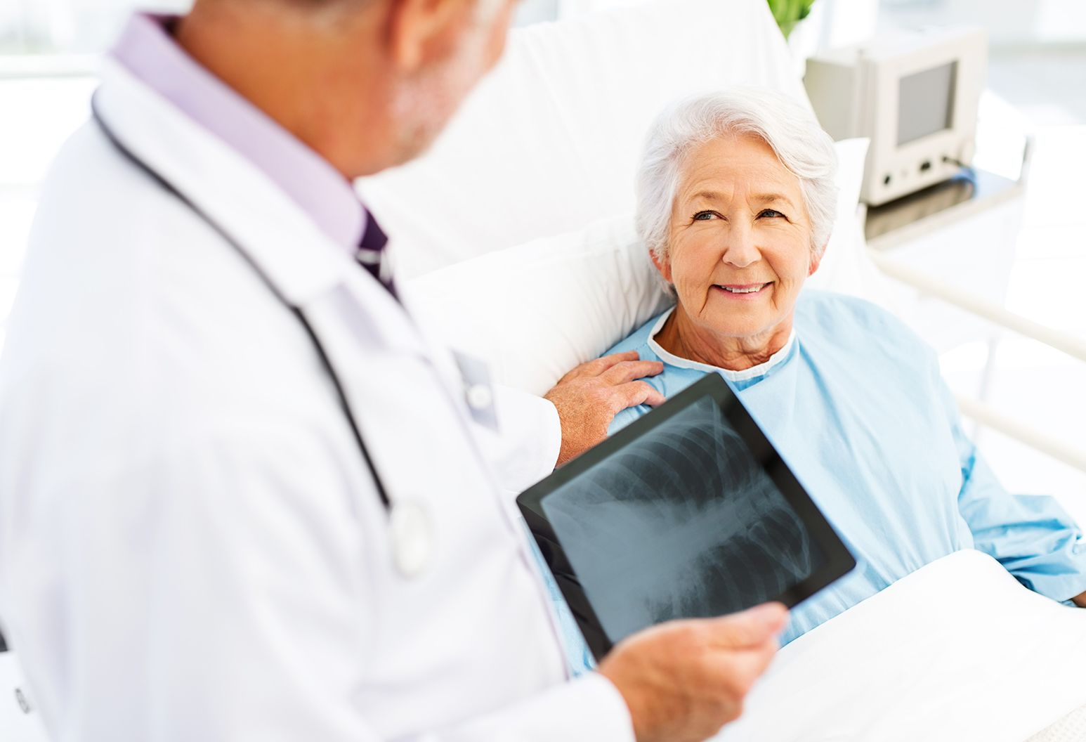 Older woman in hospital bed smiling at doctor holding a digital pad displaying chest X-ray.