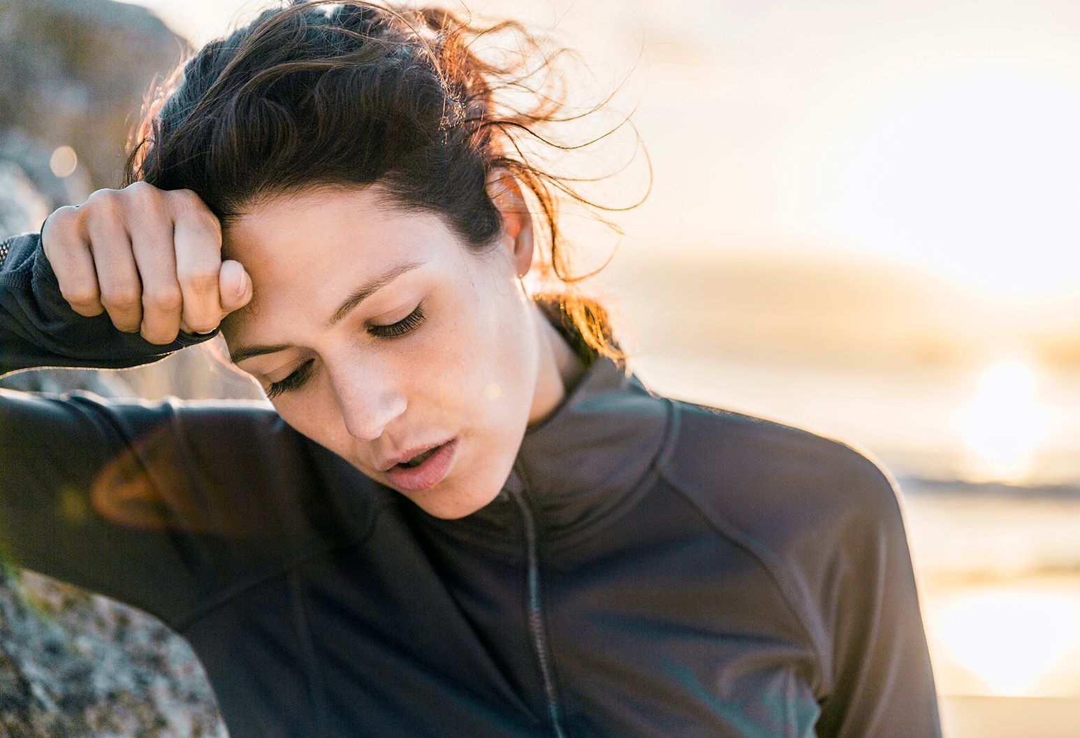 A photo of tired sporty woman looking down. Exhausted female athlete is wiping her forehead. She is wearing sportswear at beach.