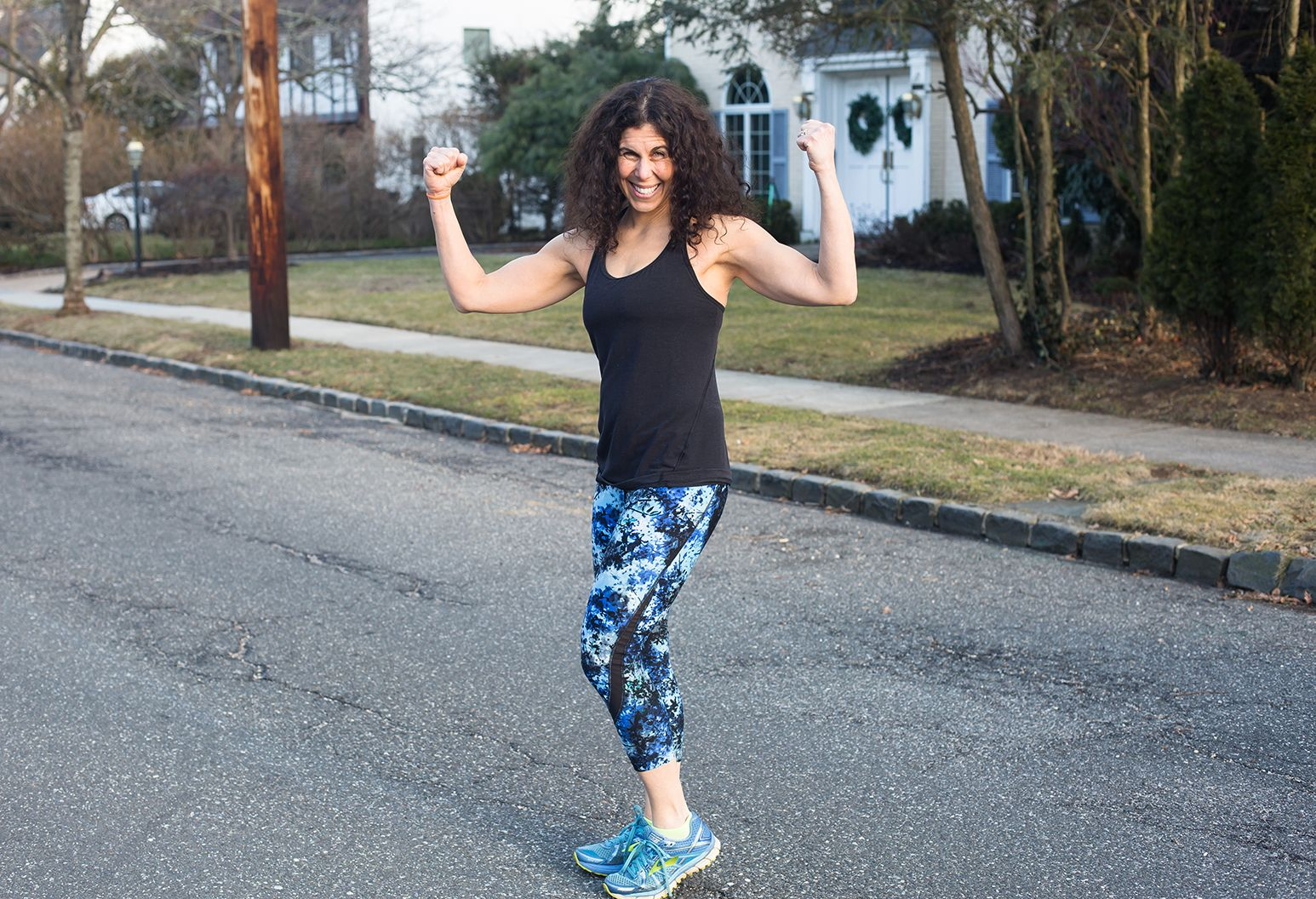 A 40 year-old woman with curly black hair wears a black tank top and black, blue and white leggins with blue sneakers. She stands in the street and poses, making muscles with her arms.